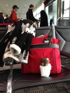 One arm for bag, 1 for coat, 1 for coffee, 1 for boarding pass. Wait a minute...